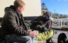 Man talking to a rough sleeper on a bench