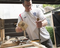 One of Langley's residents in a workshop, chiselling wood