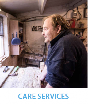 Front cover of Langley's care brochure - one of Langley's residents dressed in warm dark blue fleece is standing in a woodworking workshop, gazing out of the window