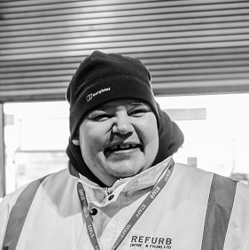 White man in a beanie hat, wearing a high vis jacket, standing in a warehouse and smiling