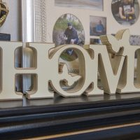 The word 'HOME' spelt out in wooden letters sitting on a dark mantelpiece. Behind it is a photo frame.