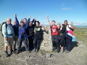 Walking group smiling at top of mountain peak
