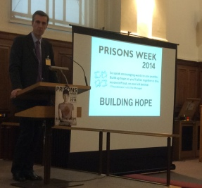 Andrew Selous MP standing on platform for Prisons Week 2014 launch