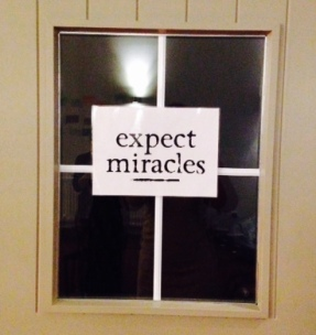 Window in a door with a sign saying 'Expect miracles'