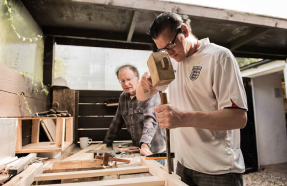 2 men in a woodwork workshop, one about to chisel some wood