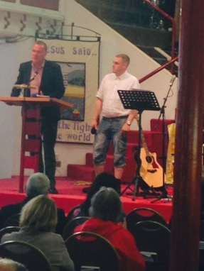 Ed, Outreach Worker and John Hamblin from Shekinah at Torbay thanksgiving service - standing on the church platform