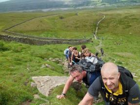 Walkers for the Yorkshire 3 Peaks 2015 looking rather pained climbing up one of the mountains