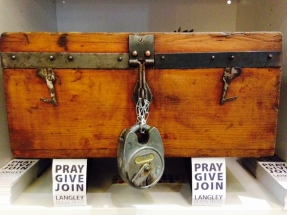 Old style wooden treasure chest with a large silver padlock on it. Around it are Langley bookmarks encouraging people to pray, give or join to help change the lives of ex-offenders