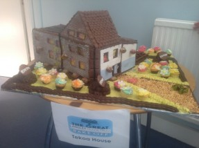 A cake in the shape of a house and surrounding gardens, highlighting Langley's values