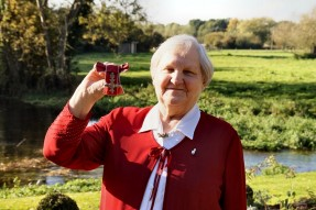 Val Dodsworth, a former Langley staff member, holding up her MBE. She is stood outside on a bright sunny day.