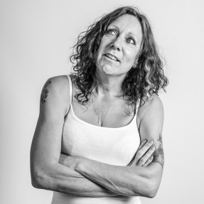 Female Langley resident in a white crop t-shirt with her arms folded across her chest