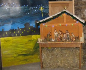 Traditional nativity scene set against a wooden background and a painting showing the Bethlehem skyline