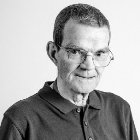 Tom Shannon, a 77 year old man, who inspired the formation of the Shannon Trust which has helped over 50,000 prisoners to read. It is a black and white photograph and Tom has short dark hair and is wearing glasses