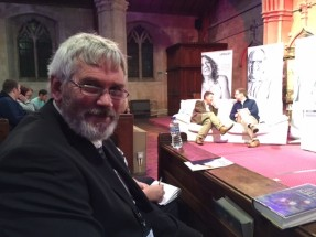Langley resident, Chris, sat on a pew whilst waiting to speak at the Langley London thanksgiving service 2016. He is looking smart in a dark suit and glasses.