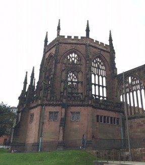 Coventry cathedral on a cold spring day. Brown brick with spires reaching into the sky.