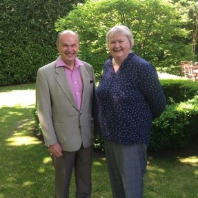 Anthony Howlett-Bolton, former Chair of Langley House Trust and Tracy Wild, CEO, stood in some gardens on a sunny day