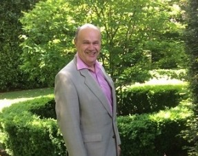 Anthony Howlett-Bolton, former Chair of Langley House Trust, stood in some gardens on a sunny day
