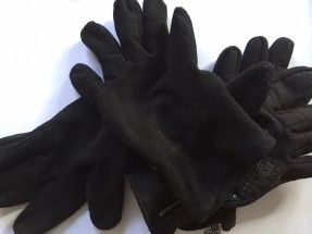 A number of black gloves laid out on a white background