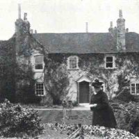 Black and white picture of Elderfield, Langley's first project. The house is covered in ivy and decorative trees and the previous owner of Elderfield, is pictured wearing a dark outfit and hat, looking towards the camera