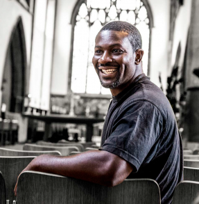 Black man sitting in a church, smiling