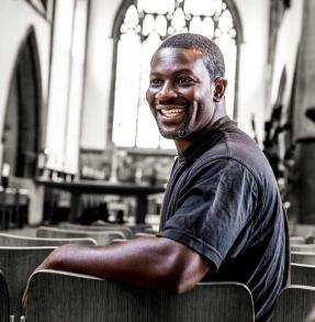 Black man sitting in a church, smiling