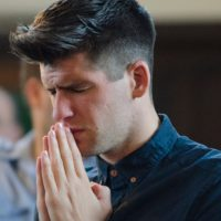 Young white man with head bowed and arms held together in prayer