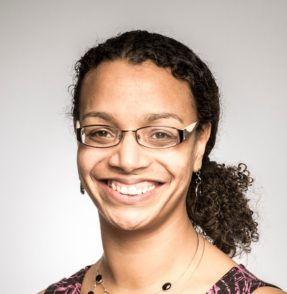 Samantha Graham, mixed race young woman with curly dark hair, wearing glasses and smiling at the camera